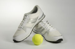 White men's sneakers and a tennis ball Stock Images