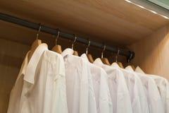 White men shirts hanging in closet Royalty Free Stock Photos