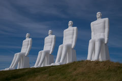 White Men statues, Esbjerg, Denmark. Four white men sitting looking at the sea near Esbjerg, Denmark. They are each 9 meters tall and made of white concrete Stock Photo