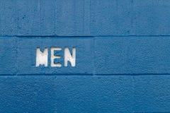 White Men text cut into blue concrete blocks stock image