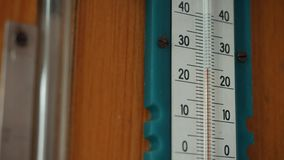 White mercury thermometer and scale on a wooden wall. Close-up.