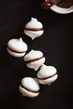 White meringue cookies with chocolate on black background. Meringue cookies with chocolate on black baking tray Royalty Free Stock Image