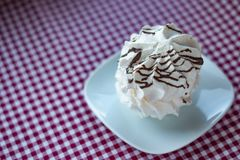 White meringue on a plate. Side view of white meringue with chocolate stripes lying on a square plate, red and white tablecloth as background, space for text and stock image
