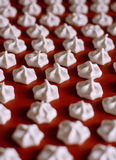 White meringue on a red baking mat Royalty Free Stock Photography