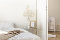 White metal bedside table with coffee mug, twig in glass vase and simple poster in frame placed by the bed. In real photo of white bedroom interior stock photos