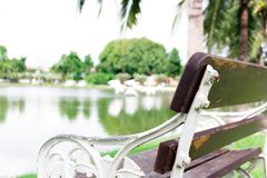 Environment of garden in the village with white metal benche and. White metal bench with old brown wooden broken seat beside the lake view Stock Photography