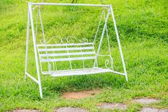 White Metal Bench Swing on Green Grass Lawn in Park. Closeup white metal bench swing on green grass lawn in tropical tourist park in Vietnam Royalty Free Stock Photography