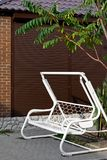White metal bench swing shed, against the background of brown wall roller blinds. Brown shingles, tree green branch, masonry, bricks brick, paving slabs, rest Royalty Free Stock Images