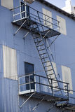 White Metal and Blue Metal Building with Fire Escape Stock Photo