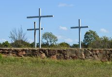 3 white metal crosses in front of a blue sky with white clouds royalty free stock images