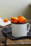 White metal cup full of orange colored macaroon cookies Stock Photos