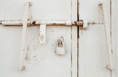 White metal door fragment with padlock. White metal door fragment with old padlock Royalty Free Stock Photography