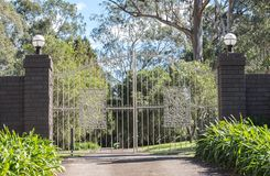 White metal driveway entrance gates set in brick fence leading to rural property with eucalyptus trees in background. White metal driveway entrance gates set in Royalty Free Stock Images