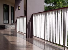 White metal fence on peaceful minimal resort hotel corridor way to rooms with shadows and reflections. On ceramic floor open space semi-outdoor scene under Stock Photography