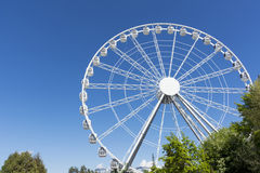 White metal Ferris wheel with cabins on background of blue sky, royalty free stock image