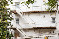 White Metal Fire Escape on Old White Building. By trees Stock Photos