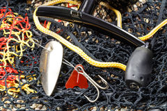White metal fishing bait with spinning reel and fish tank on the stony ground Royalty Free Stock Image