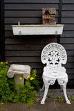 White Metal Garden Chair next to Small Column and Birdhouse Stock Images
