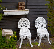 White Metal Garden Chairs next to Small Column and Birdhouse Stock Photo