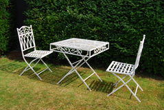 White metal garden furniture table and two chairs. White metal garden furniture - table and two chairs on a grass lawn Stock Photos