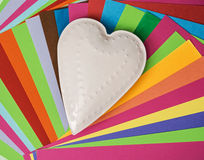 White metal heart on a colorful papers Stock Photography