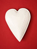 White metal heart on the red background Stock Photo