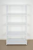 White metal rack near the wall, empty shelves Royalty Free Stock Photo