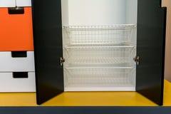 White metal rack shelves inside the modern wooden cabinet Royalty Free Stock Photos