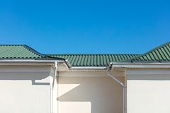 White metal rain gutter system on roof top of new house stock images