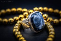 White metal ring with big blue stone gold beads royalty free stock photos