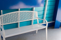 White metal seat beside blue wall Royalty Free Stock Photo
