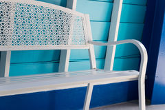 White metal seat beside blue wall Stock Photography