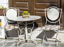 White metal table with two chairs.Cozy restaurant Stock Image