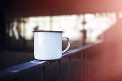 White metal tea cup on the rails. Blurred background. 3d rendering Stock Photo