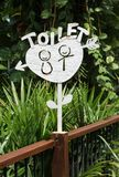 White metal TOILET sign. Stand on wooden pole in the hotel resort Stock Photos