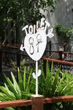 White metal TOILET sign. Stand on wooden pole in the hotel resort Royalty Free Stock Photos