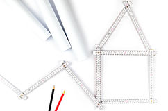 White meter tool forming a house, two drawing pencils and paper Royalty Free Stock Photography