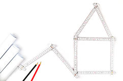White meter tool forming a house, two drawing pencils and paper Royalty Free Stock Photo