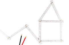 White meter tool forming a house, two drawing pencils on white Royalty Free Stock Images