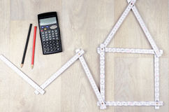 White meter tool forming a house, two pencil and calculator on w Stock Photos