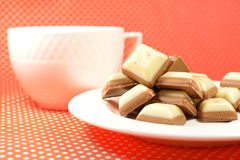 White and milk chocolate sweets. On a white plate with a cup on a red tablecloth Stock Photos