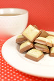 White and milk chocolate sweets. On a white plate with a cup on a red tablecloth Stock Photography