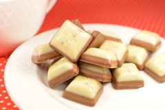White and milk chocolate sweets. On a white plate on a red tablecloth Stock Photos