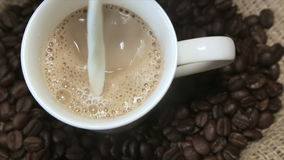 White milk in a cup of cappuccino. Coffee bean stock video footage