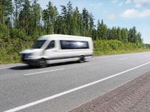 White mini bus  on country highway, motion blur. White mini bus speeding on summer country highway, blured in motion Stock Photos