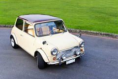 White mini car. Classic white mini car on road with grass in background Royalty Free Stock Image