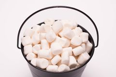 White mini marshmallows background close-up texture. A pile of. Mini white puffy marshmallows in black bowl on white background. Marshmallow concept. Wallpaper stock photography