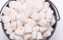 White mini puffy marshmallows ia a black bowl on white backgroun. D with copy spase. Top view, close-up stock photo