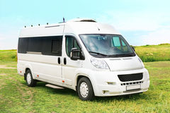 White minibus on in the field. Against the sky Stock Image