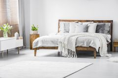 White minimal bedroom interior. White knit blanket on wooden bed in minimal bedroom interior with flowers on cupboard Royalty Free Stock Photo